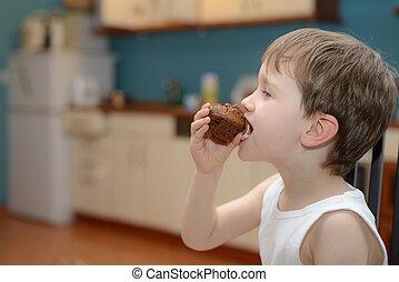 4 year old boy eats chocolate muffin