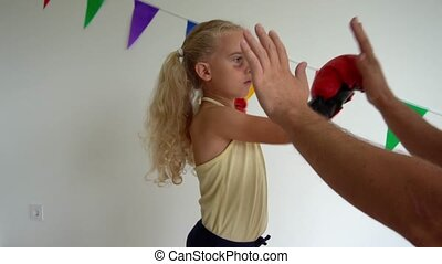 4 years old daughter boxing, training with dad father at home. Bruise on child face. Gimbal movement slow motion shot.