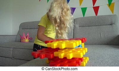 4 years old girl play on sofa. Creative child assembly game...
