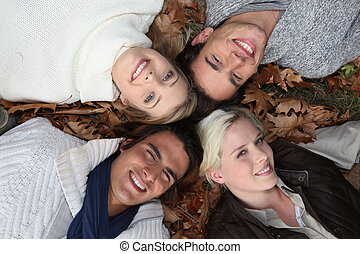 4 young people heads in the grass at autumn
