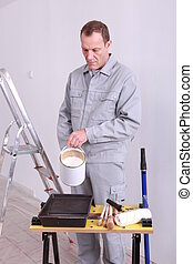 45 years old house painter is putting paint in a box