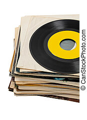 45s Vinyl Records stack with old dusty album sleeves on white background. Selective focus.