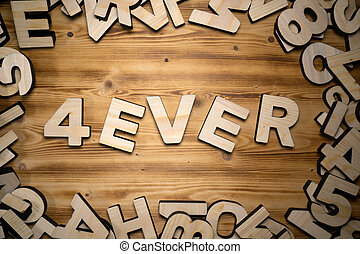 4EVER word made with block letters lying on wooden board