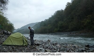 4k. a guy near a tourist tent on the bank of a mountain...