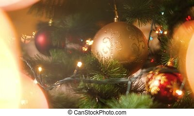 4k abstract footage of decorated Christmas tree with baubles and garlands. Glowing LED lights on the foreground