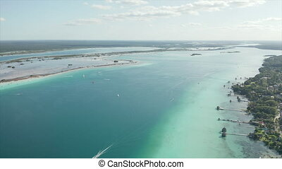 4k drone video overlooking several boats moving in crystal clear Lago Bacalar, Mexico - near the border with Belize