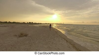 4k aerial - Attractive Girl Turns Goes Along a Sandy Beach at sunset.