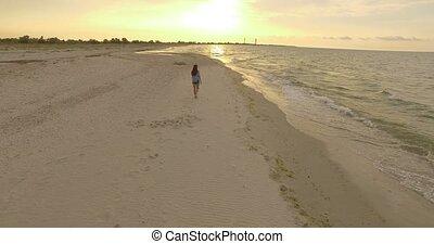 4k aerial - Beautiful Girl Walks Along a Sandy Beach at sunset.