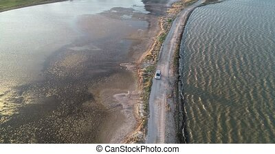 4K aerial drone view of Azov liman coastline. Offroad car...