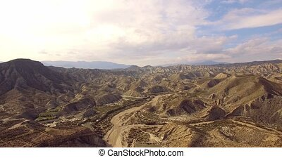 4K Aerial, Flight over a dry riverbed in a desert in...