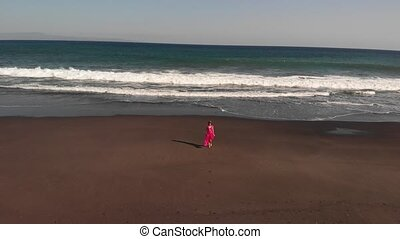 4K Aerial flying footage of young woman in pink dress...