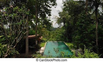 4K aerial flying video of infinity swimming pool at luxury...