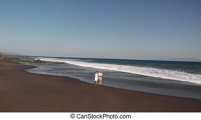 4K aerial flying video of young couple on the beach with...