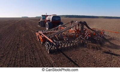 4k aerial footage of a modern tractor plowing dry field, preparing land for sowing