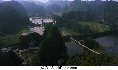 4K Aerial footage of Tam Coc homestay and rice fields during sunset in Ninh Binh