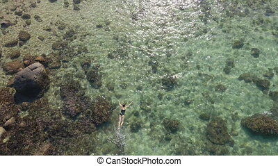 4K aerial shot of a young woman snorkeling in a clear blue sea water