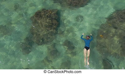 4K aerial slowmotion shot of a young woman snorkeling in a clear blue sea water