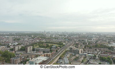 4k Aerial Amazing View Moving Around East London, showing a train goes by and skyscrapers as background on a sunny day