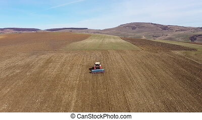4k Aerial top view of a tractor, combine harvester plowing...
