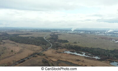 4k aerial video moving over lands towards an industrial area with smoke stacks, showing a cloudy sky in the background