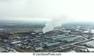 4k aerial footage flying toward an industrial smoke stack while cars driving by, showing a scenic view of the city