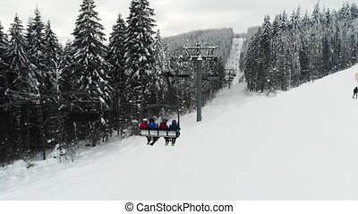 4k aerial view of people moving on chair lift