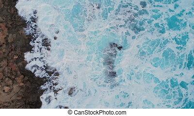 4k Aerial view of sea waves break on stone beach