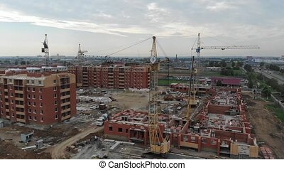 4k Aerial view of the city. Tower cranes working at a construction site