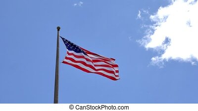 4K American flag - star and stripes floating over a cloudy...