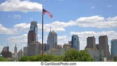 4K American flag stars and stripes floating in front of the - Philadelphia skyline - Pennsylvania - USA