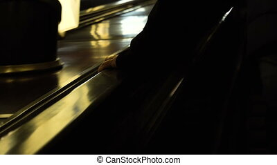 4K Anonymous mans hand holding an escalator going up as blurred passengers descend on the other side in slow motion, shot on RED EPIC