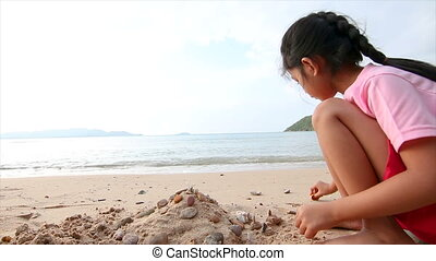 4K Asian little girl playing on the beach