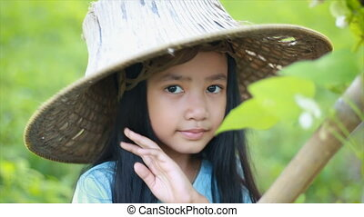 4K Asian little girl wearing farmer hat in green nature farm with happiness