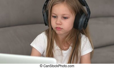 4K: attractive European girl is listening to music on a computer with headphones singing and dancing in the room