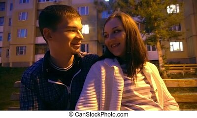 4k attractive young Couple in love at park bench hug, cuddle, embrace.Happy,in love,male and female couple in their 20's and 30's laugh hug and cuddle tracking shot