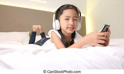 4k, aziaat, klein meisje, het luisteren, witte , hoofdtelefoon, met, geluk