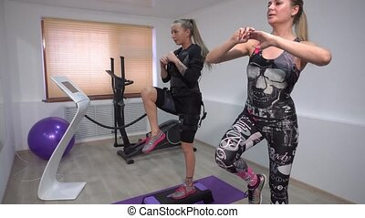 4k Beautiful athletic girl in EMS suit does exercises with a...