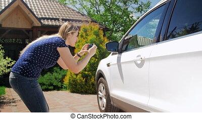 4k, beeldmateriaal, van, jonge vrouw , vervaardiging, foto's, van, haar, auto, op, smart, telefoon, voor, het verkopen, informatietechnologie