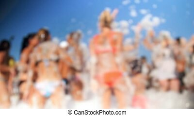 4k blurred video of cheerful crowd dancing on the soap beach party. Soap bubbles flying around.