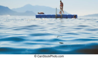 4k blurred video of people swimming and climbing on floating...