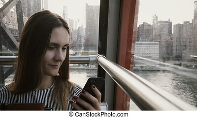 4K Business woman typing in air funicular cabin. New York,...