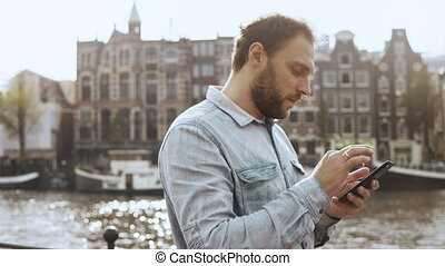 4K Caucasian businessman texting near river. Panning shot. 30s serious bearded man in blue shirt sending email messages.