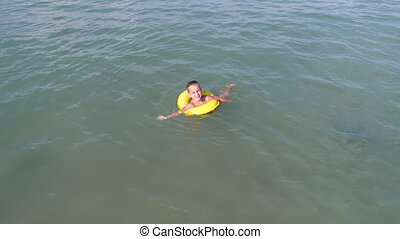 A young simpotic boy is floating in blue sea water.