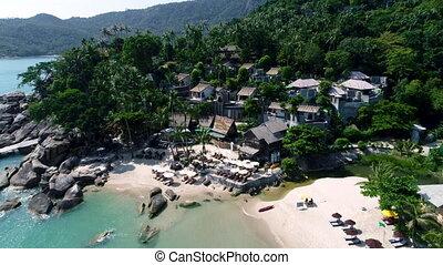 The camera flies around the small round tropical island...
