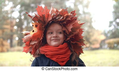 4k close-up portrait of smiling cute little girl in a wreath crown of autumn maple leaves posing, making funny faces