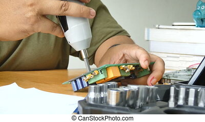 4K Close up shot hands of mechanic man using electric screwdriver to spin the screw on electronic print circuit board with ambient sound