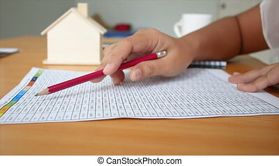 4K Close up shot hands of woman reading to number in the paper on table