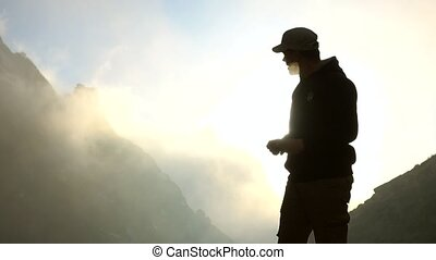 4K close up shot of a man making mobile phone pictures high in the mountains