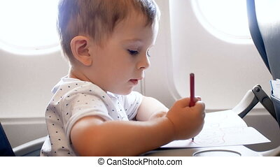 4k closeup footage of adorable 2 years old toddler boy drawing with colorful pencils during flight in airplane