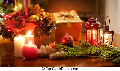 4k closeup footage of burning candles, gifts and Christmas decorations on table against fireplace at living room. Perfect background for winter celebrations and holidays